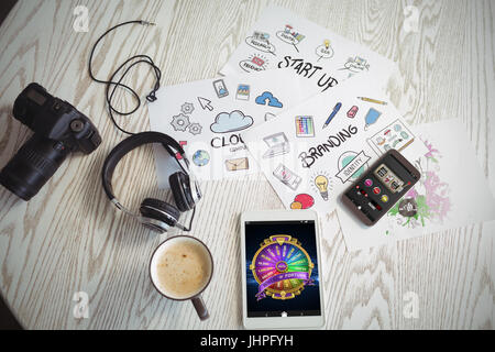 Colorful wheel of fortune on mobile display against various technologies with colorful charts and coffee on table - Stock Photo