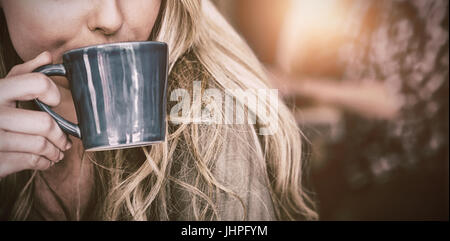 Close up of young woman drinking coffee in cafe - Stock Photo