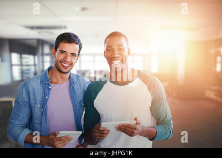 Smiling businessmen are using a digital tablet against table and empty chairs in office - Stock Photo