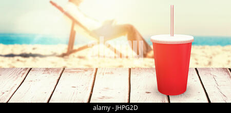 Young businessman resting on his deck chair using his tablet against red cup over white background - Stock Photo