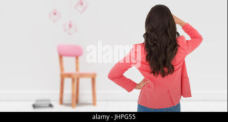 Elegant brunette standing back to camera and looking away against decoration over empty wooden chair and books against - Stock Photo