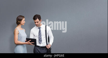 Businessman is touching on the screen while a woman is holding the tablet  against grey background - Stock Photo