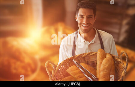 Baker holding bread in whisker basket  against michetta and sweet food on table - Stock Photo