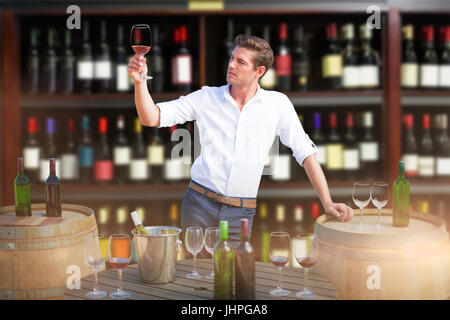 Young man holding red wine glass by barrels against wine bottles arranged on shelves - Stock Photo