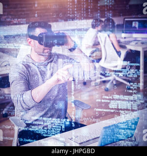Male executive using virtual reality headset in office - Stock Photo