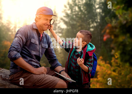 A little boy showing magnifying glass to his father  against autumn trees in forest - Stock Photo