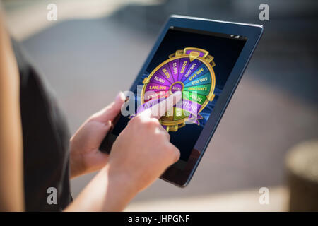 Colorful wheel of fortune on mobile display against businesswoman using digital tablet - Stock Photo