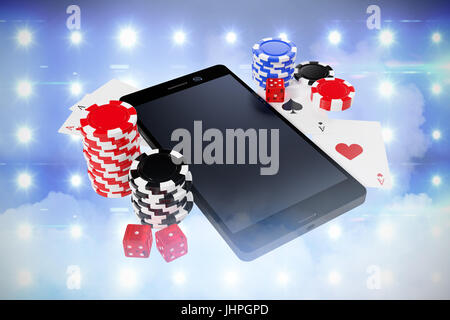 Smartphone with playing cards and casino tokens against illuminated blue floodlight - Stock Photo