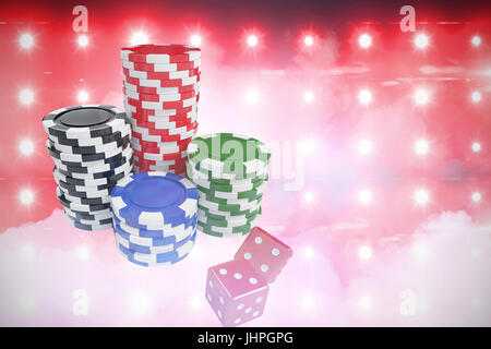 Stack of colorful casino tokens by dice against green floodlight at night - Stock Photo