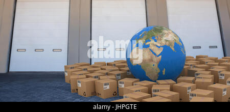 3D image of globe amidst cardboard boxes against closed door of warehouse - Stock Photo