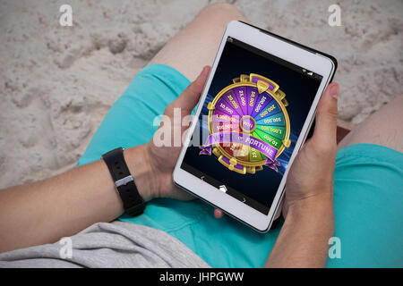 Colorful wheel of fortune on mobile display against man using digital tablet on the beach - Stock Photo