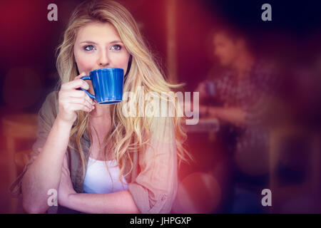 Young woman drinking coffee with man sitting in background at cafe - Stock Photo