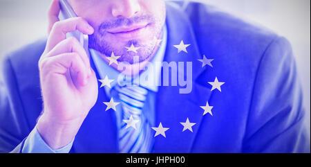 Handsome businessman sitting on sofa making a call against european flag - Stock Photo