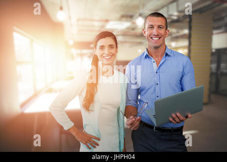 Smiling business people using a laptop against tables in office cafeteria - Stock Photo