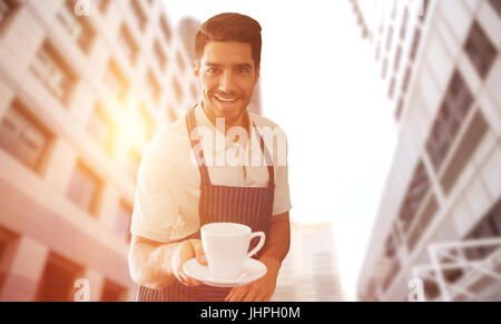 Waiter pointing a cup of coffee  against low angle view of office towers - Stock Photo