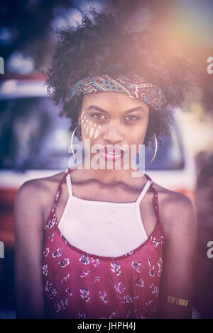 Portrait of young woman standing against van on field - Stock Photo