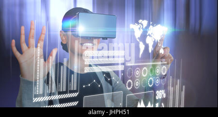 Smiling woman gesturing while wearing black virtual reality glasses against tables in office cafeteria - Stock Photo