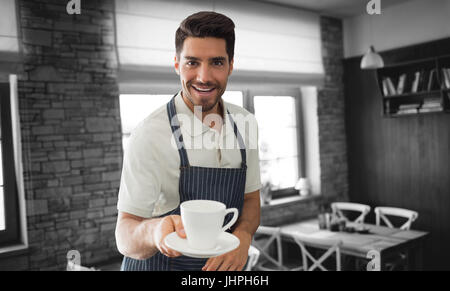 Waiter pointing a cup of coffee  against empty chairs and tables - Stock Photo