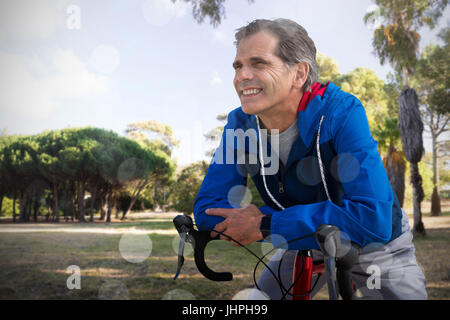 Digital composite of senior man with his bike against trees growing at park against sky - Stock Photo