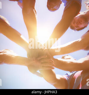 Low angle view of rugby team holding hands while standing against clear sky - Stock Photo