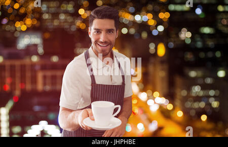 Waiter pointing a cup of coffee  against defocused image of illuminated buildings - Stock Photo