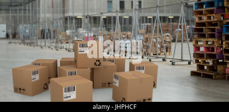 Group of composite cardboard boxes against image of a warehouse - Stock Photo