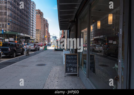 New York , NY USA -- July 12, 2017 -- Sidewalk signs and stores along a busy 7th Avenue in New York's Greenwich - Stock Photo