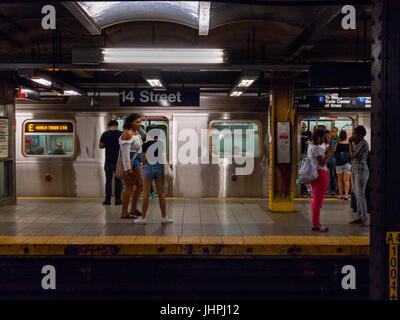 New York, NY USA -- July 12, 2017 -- People are waiting on the platform of the 14th Street staiton as a train pulls - Stock Photo