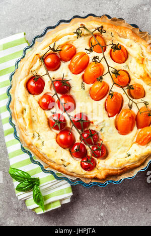 Homemade freshly prepared tart with tomatoes and sheep cheese on a gray background. - Stock Photo