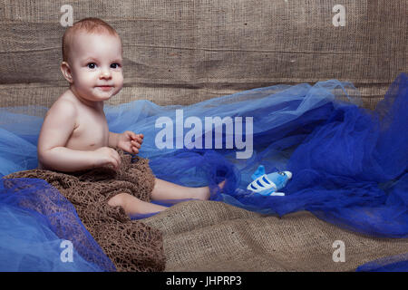 Beautiful baby girl sitting. She is wrapped  with a grid - Stock Photo
