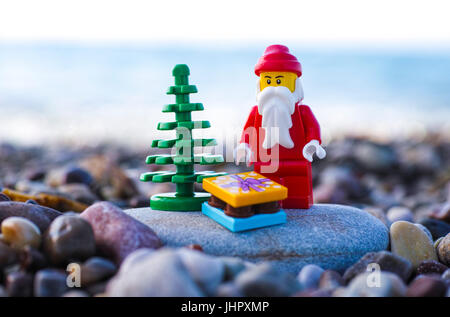 Paphos, Cyprus - November 20, 2016 Lego Santa Claus minifigure with Christmas tree and present stand on pebble beach - Stock Photo