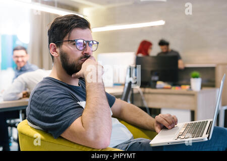 Photo bearded banker working in a modern office overtime. Man sitting in yellow chair at night. Using contemporary - Stock Photo