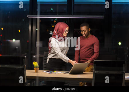 Arab woman and African man collaborating in the office working overtime. - Stock Photo