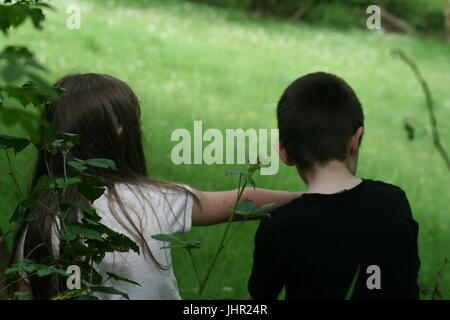 brother and sister sat together outside - Stock Photo