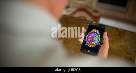 Colorful wheel of fortune on mobile display against cropped image of man holding phone - Stock Photo