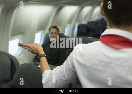 Air hostess gives safety instructions on board in an aircraft - Stock Photo
