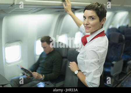 Confident air hostess smiling at camera while passenger reading magazine in an aircraft - Stock Photo