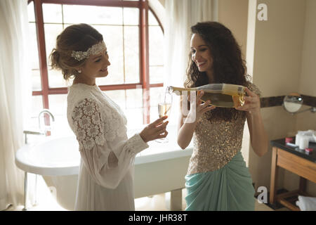 Bridesmaid pouring champagne in bride glass at home - Stock Photo