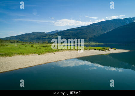 Scenic view of sea by mountain against blue sky - Stock Photo