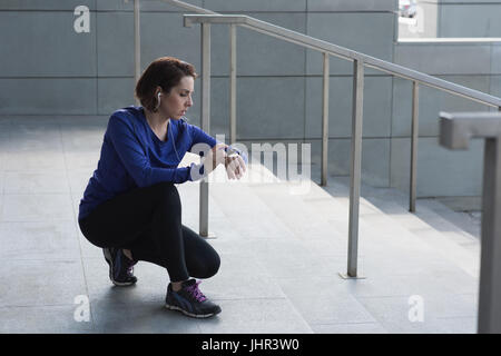 Fit woman checking time on staircase - Stock Photo