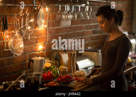 Smiling woman preparing food while standing in kitchen at home - Stock Photo