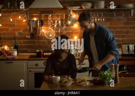 Smiling man serving food for woman while sitting at table in kitchen - Stock Photo
