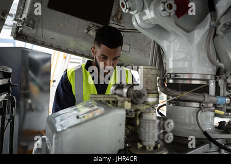 Aircraft maintenance engineers examining turbine engine of aircraft ...