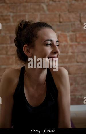 Beautiful woman relaxing in fitness studio - Stock Photo