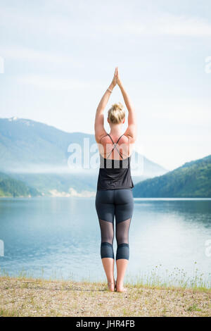 young attractive woman in urdhva dhanurasana pose against