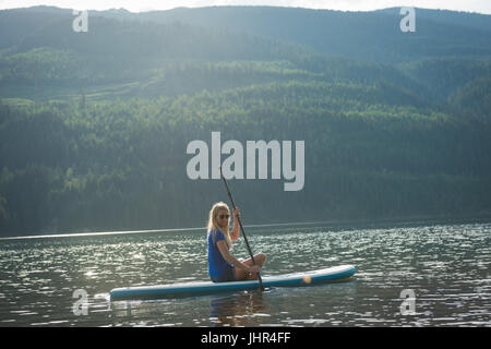 Side view of woman sitting on paddleboard in lake against mountain - Stock Photo