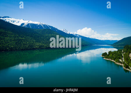 Scenic view of lake by mountain against blue sky - Stock Photo