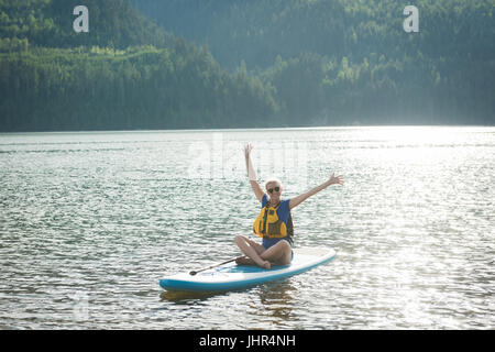 Excited young woman sitting with arms raised on paddleboard in lake - Stock Photo