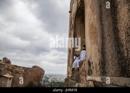 Two friends rest in traditional clothes on top of Golconda Fort, while one talks over the phone. - Stock Photo