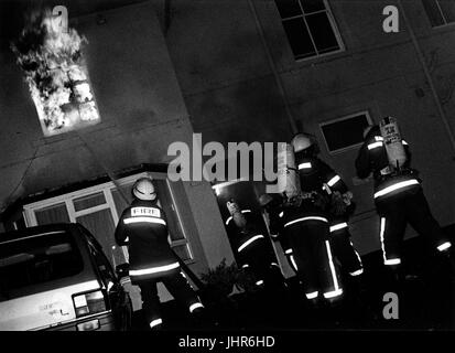 Fire Fighters of West Midlands Fire Brigade enter burning building in search of a 'persons reported' - Stock Photo
